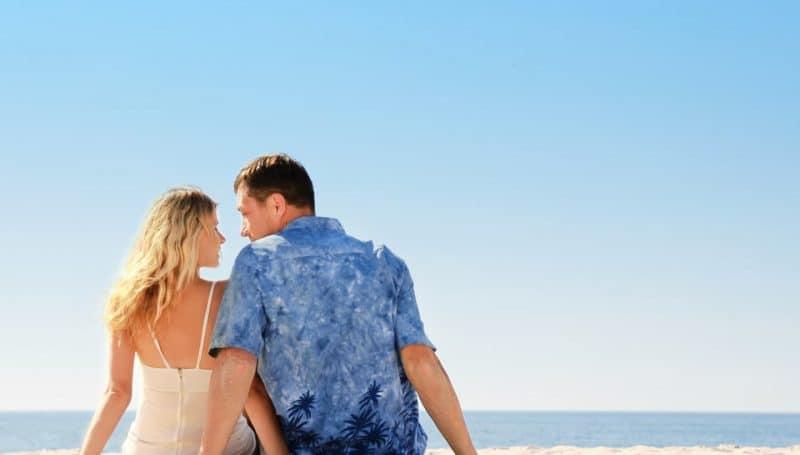 pregnant couple sitting on beach